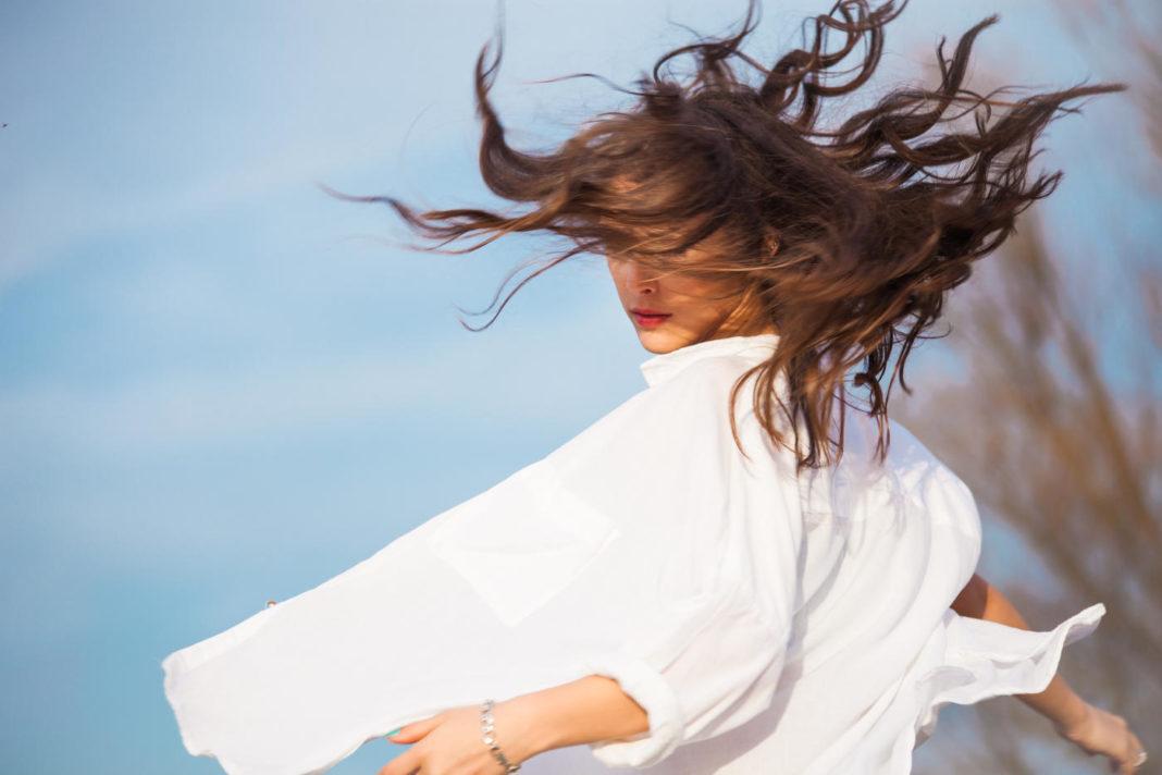 jeune femme dans une chemise blanche qui se tourne avec les cheveux en mouvement, en extérieur, le ciel bleu en fond