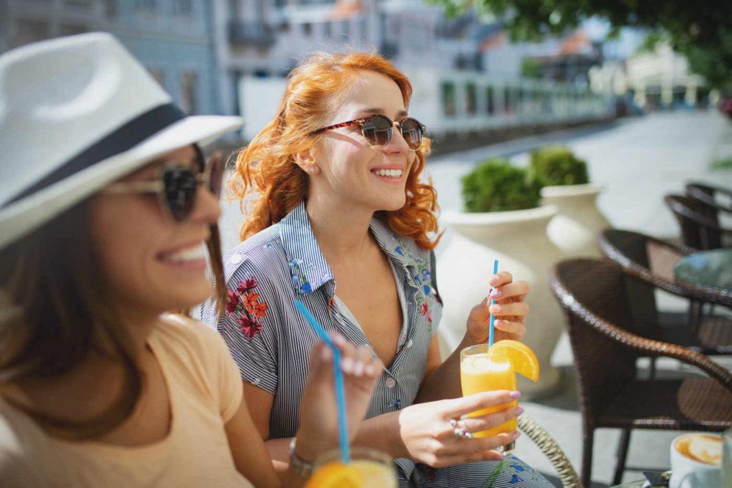 terrasse à Montpellier - 2 jeunes femmes assisses à une terrasse en extérieur en train de boire un jus d'orange